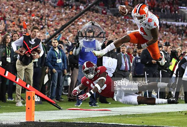 Quarterback Deshaun Watson of the Clemson Tigers is stopped short of the goal line by defensive back Ronnie Harrison of the Alabama Crimson Tide...