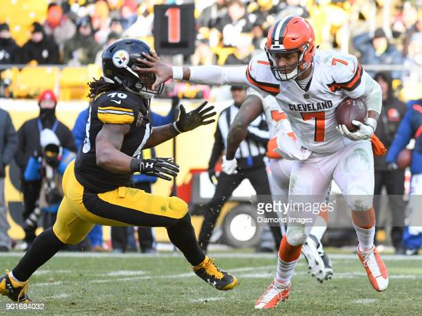 Quarterback DeShone Kizer of the Cleveland Browns stiffarms linebacker Bud Dupree of the Pittsburgh Steelers as he carries the ball downfield in the...
