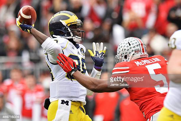 Quarterback Devin Gardner of the Michigan Wolverines tosses a 12yard touchdown pass as he is rushed by Raekwon McMillan of the Ohio State Buckeyes in...
