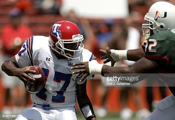 Quarterback Donald Allen of Louisiana Tech dodges defensive linemen Orien Harris of the University of Miami in the first quarter on September 18,...