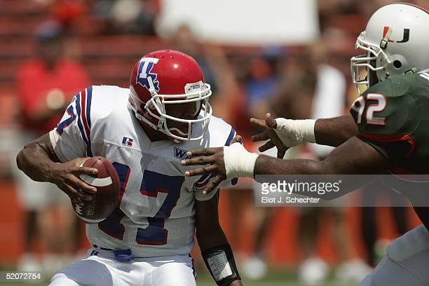 Quarterback Donald Allen of the Louisiana Tech Bulldogs tries to avoid defensive lineman Orien Harris of University of Miami Hurricanes during the...