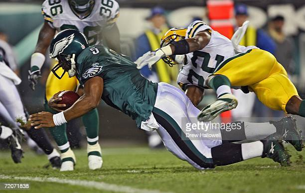 Quarterback Donovan McNabb of the Philadelphia Eagles dives into the endzone for a touchdown while getting hit by safety Marquand Manuel of the Green...