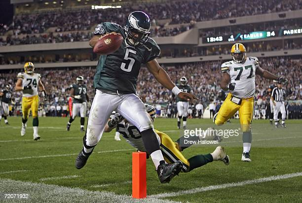 Quarterback Donovan McNabb of the Philadelphia Eagles jumps into the end-zone for a touchdown while getting hit from behind by linebacker A.J. Hawk...
