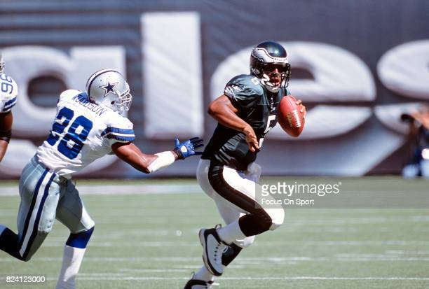 Quarterback Donovan McNabb of the Philadelphia Eagles runs with the ball pursued by Darren Woodson of the Dallas Cowboys during an NFL game September...