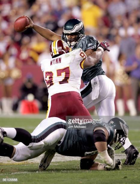 Quarterback Donovan McNabb of the Philadelphia Eagles scrambles under pressure from defensive end Renaldo Wynn of the Washington Redskins on November...