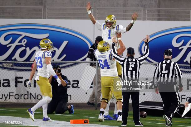 Quarterback Dorian Thompson-Robinson of the UCLA Bruins is hoisted by offensive lineman Sam Marrazzo after scoring on a 11-yard rushing touchdown...