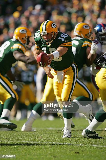 Quarterback Doug Pederson of the Green Bay Packers attempts a handoff against the New York Giants during the game on October 3 2004 at Lambeau Field...