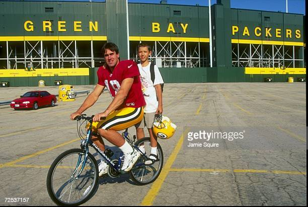 Quarterback Doug Pederson of the Green Bay Packers gives a fan a ride on a bike during the Packers Training Camp at Lambeau Field in Green Bay...