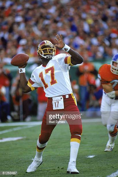 Quarterback Doug Williams of the Washington Redskins looks to pass during Super Bowl XXII against the Denver Broncos at Jack Murphy Stadium on...