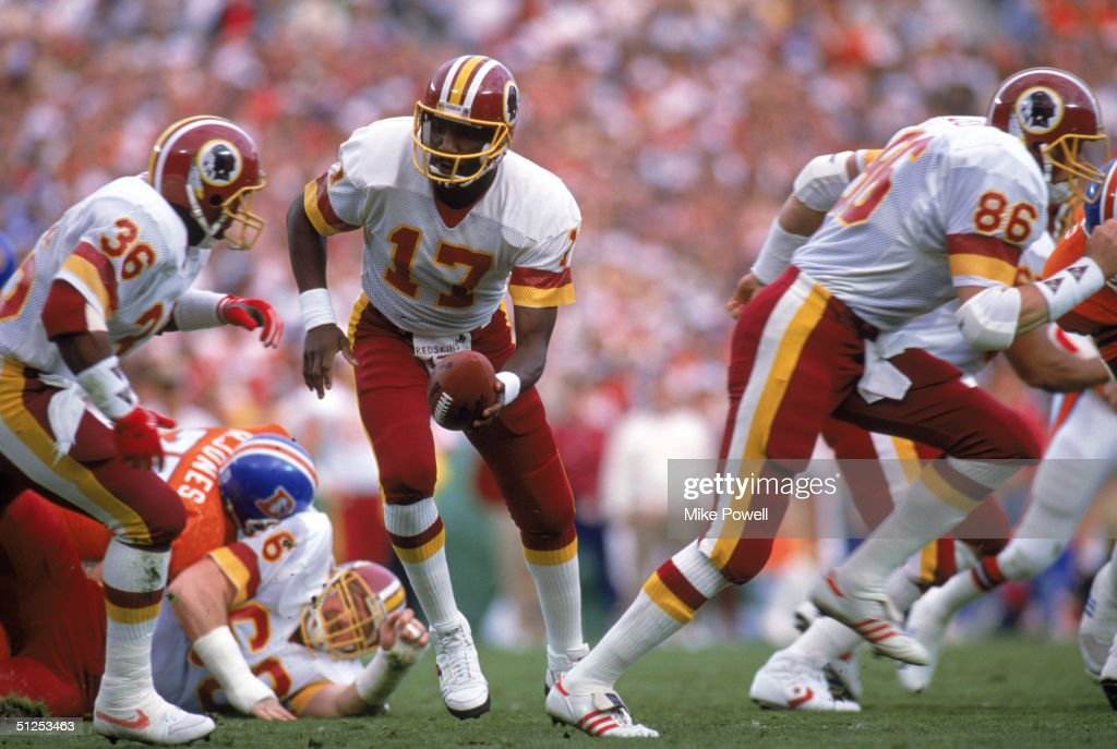 Quarterback Doug Williams #17 of the Washington Redskins prepares to hand of the ball to running back Timmy Smith #36 during Super Bowl XXII against the Denver Broncos at Jack Murphy Stadium on January 31, 1988 in San Diego, California. The Redskins won 42-10.