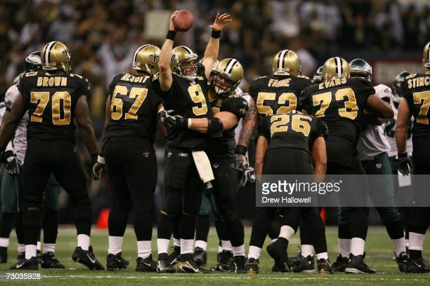 Quarterback Drew Brees and running back Mike Karney of the New Orleans Saints celebrate the divisional playoff win at the end of the game against the...