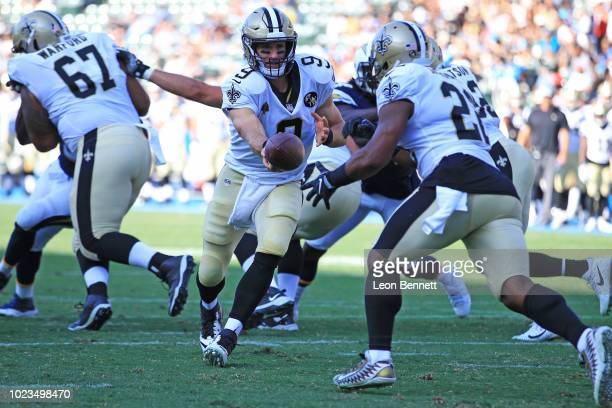 Quarterback Drew Brees hands the ball off to running back Mark Ingram of the New Orleans Saints against the Los Angeles Chargers during a preseason...