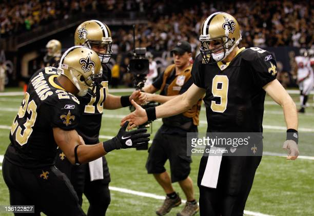 Quarterback Drew Brees of the New Orleans Saints celebrates throwing a 24yard third quarter touchdown pass with running back Pierre Thomas and...
