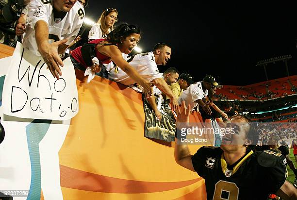 Quarterback Drew Brees of the New Orleans Saints celebrates with Saints' fans after his team's victory over the Miami Dolphins at Land Shark Stadium...