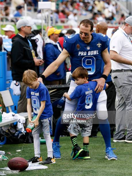 Quarterback Drew Brees of the New Orleans Saints from the NFC Team on the sidelines with his sons Bowen and Callen Brees during the NFL Pro Bowl Game...