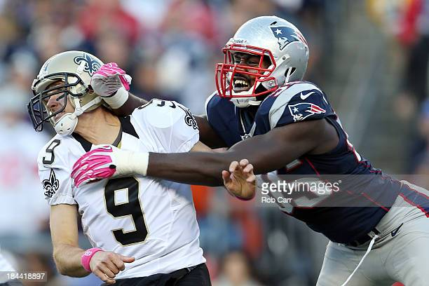 Quarterback Drew Brees of the New Orleans Saints gets off a pass while being hit by defensive end Chandler Jones of the New England Patriots during...