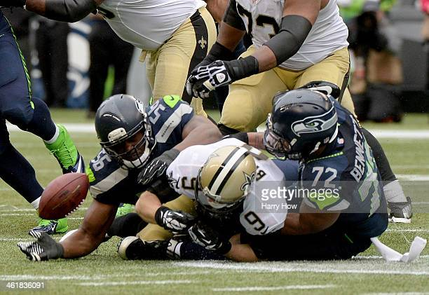 Quarterback Drew Brees of the New Orleans Saints is sacked by defensive end Cliff Avril and defensive end Michael Bennett of the Seattle Seahawks in...