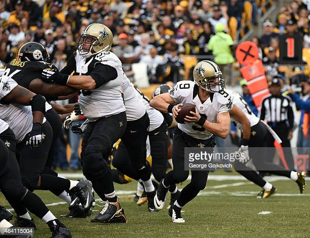 Quarterback Drew Brees of the New Orleans Saints looks to hand off the football as center Jonathan Goodwin blocks during a game against the...