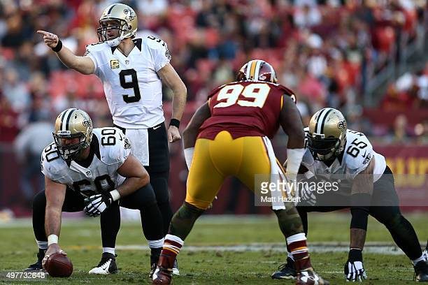 Quarterback Drew Brees of the New Orleans Saints signals before a snap from center Max Unger of the New Orleans Saints while guard Senio Kelemete of...