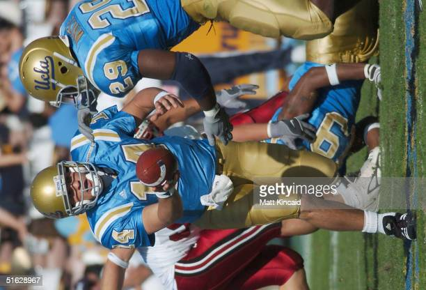 Quarterback Drew Olson hands the ball off to Manuel White of the UCLA Bruins during the game against the Stanford University Cardinals at the Rose...