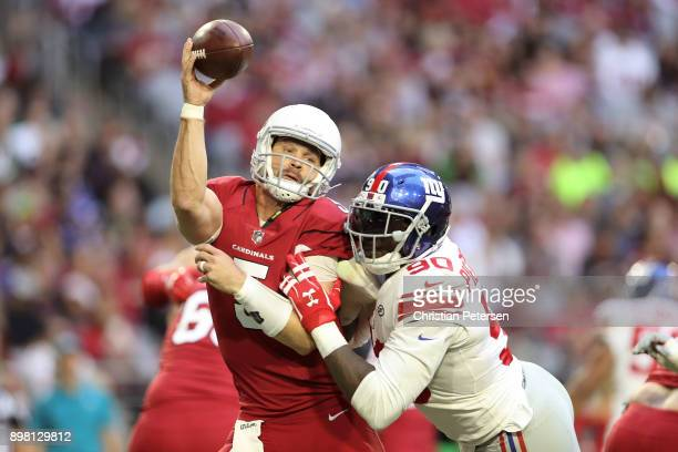 Quarterback Drew Stanton of the Arizona Cardinals is hit by defensive end Jason PierrePaul of the New York Giants while throwing a pass in the first...