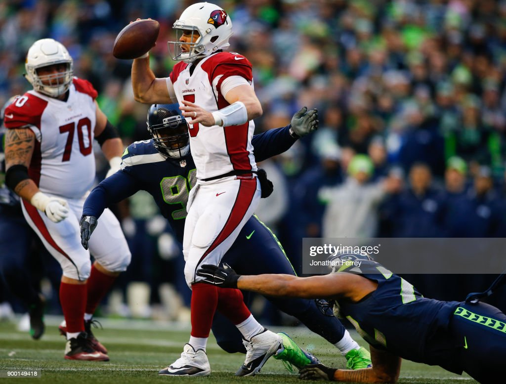Quarterback Drew Stanton #5 of the Arizona Cardinals is pressured by Garrison Smith #98 of the Seattle Seahawks and Michael Bennett #72 in the third quarter at CenturyLink Field on December 31, 2017 in Seattle, Washington.