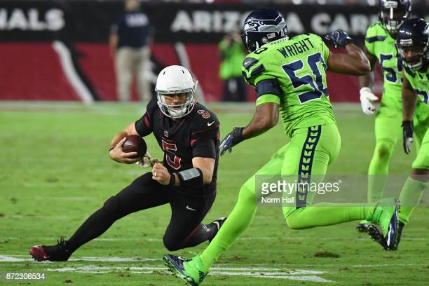 Quarterback Drew Stanton of the Arizona Cardinals scrambles with the football in front of outside linebacker KJ Wright of the Seattle Seahawks in the...