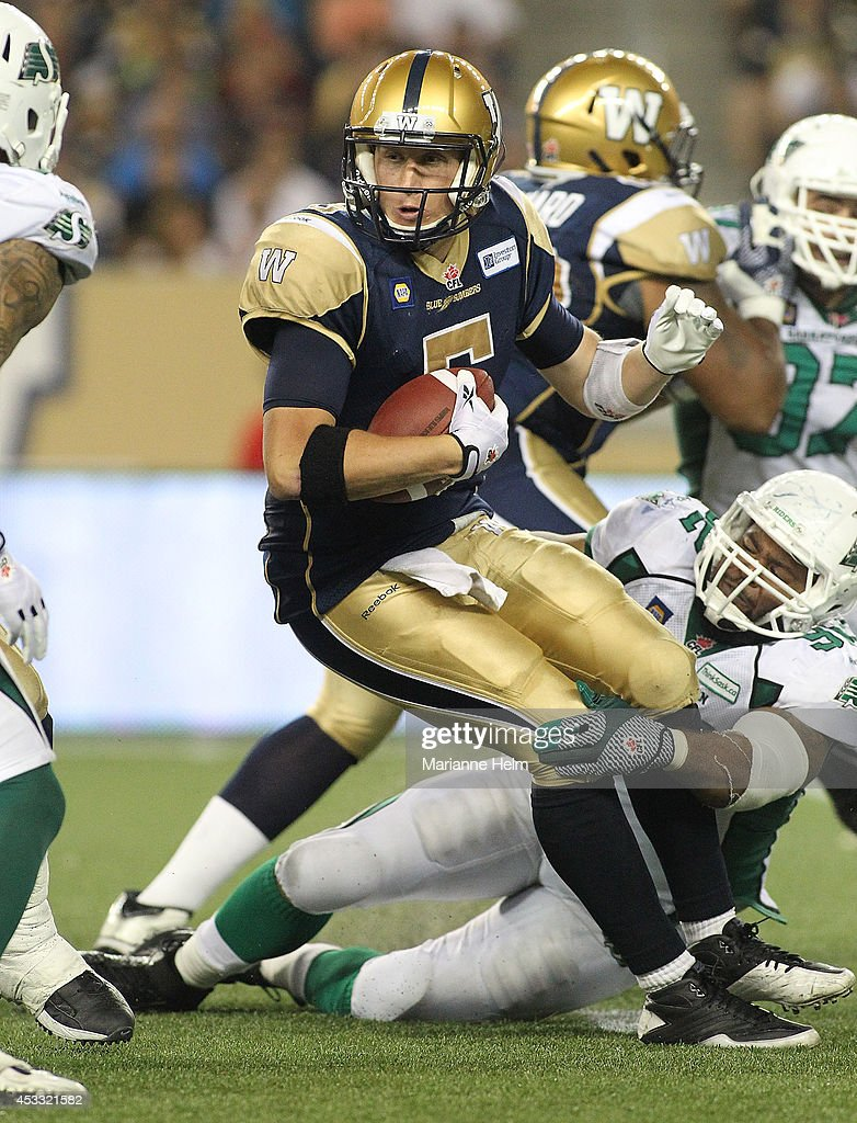 Quarterback Drew Willy #5 of the Winnipeg Blue Bombers is held by Trevor Guyton #92 of the Saskatchewan Roughriders in second-half action in a CFL game at Investors Group Field on August 7, 2014 in Winnipeg, Manitoba, Canada.