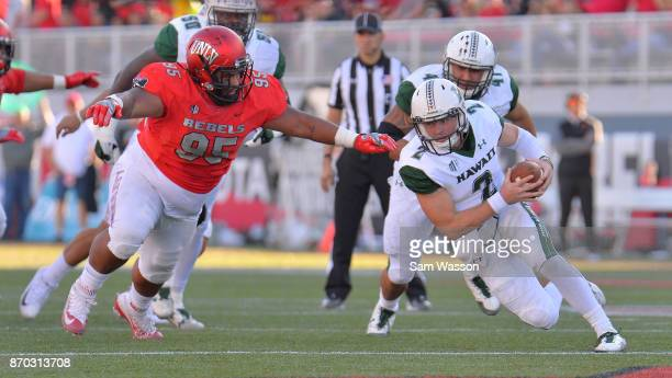 Quarterback Dru Brown of the Hawaii Warriors runs for a gain against defensive lineman Jason Fao of the UNLV Rebels during their game at Sam Boyd...