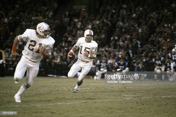Quarterback Earl Morrall of the Miami Dolphins rolls out to pass as runningback Jim Kiick provides blocking during a game on October 29 1972 against...