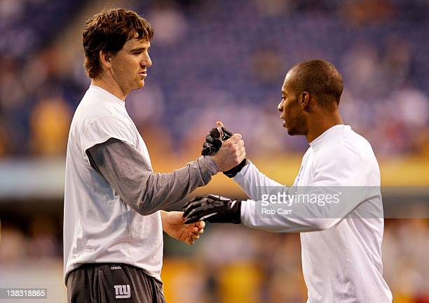 Quarterback Eli Manning of the New York Giants and Victor Cruz work out on the field during warmups before the New York Giants take on the New...