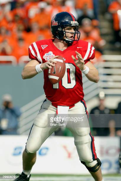 Quarterback Eli Manning of the Mississippi Rebels looks for the open receiver during the SBC Cotton Bowl against the Oklahoma State Cowboys on...