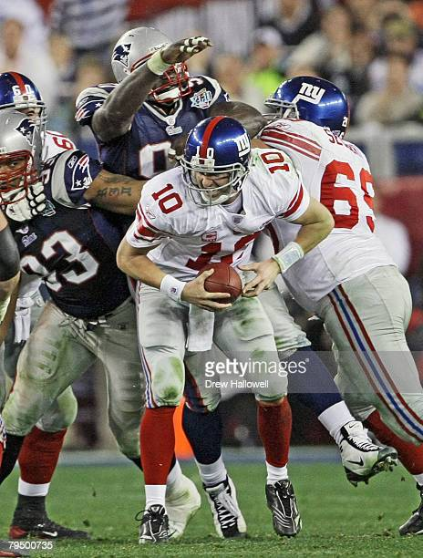 Quarterback Eli Manning of the New York Giants avoids a sack in the fourth quarter during Super Bowl XLII on February 3 2008 at University of Phoenix...