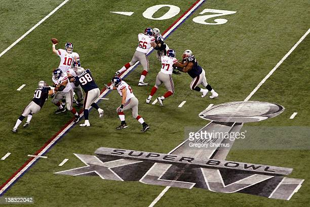 Quarterback Eli Manning of the New York Giants drops back to pass during the first quarter against the New England Patriots during Super Bowl XLVI at...