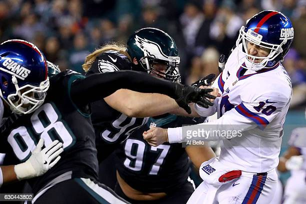 Quarterback Eli Manning of the New York Giants gets hit by defensive tackle Beau Allen of the Philadelphia Eagles after a pass during the fourth...