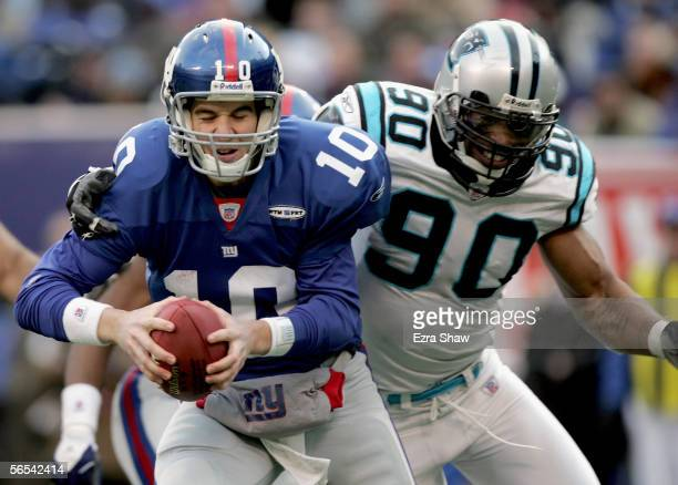 Quarterback Eli Manning of the New York Giants gets sacked by Julius Peppers in the fourth quarter of the NFC Wild Card Playoff Game against the...