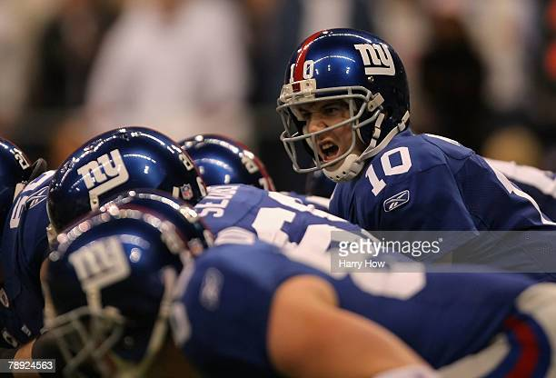 Quarterback Eli Manning of the New York Giants hikes the ball against the Dallas Cowboys in the NFC Divisional Playoff game at Texas Stadium on...