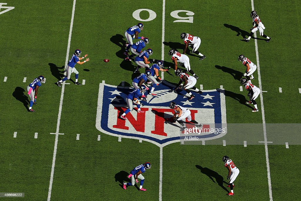 Quarterback Eli Manning #10 of the New York Giants hikes the ball in the fourth quarter against the Atlanta Falcons during their game at MetLife Stadium on October 5, 2014 in East Rutherford, New Jersey.