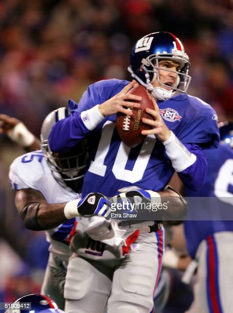 Quarterback Eli Manning of the New York Giants is sacked by defensive end Marcellus Wiley of the Dallas Cowboys at Giants Stadium on January 2, 2005...
