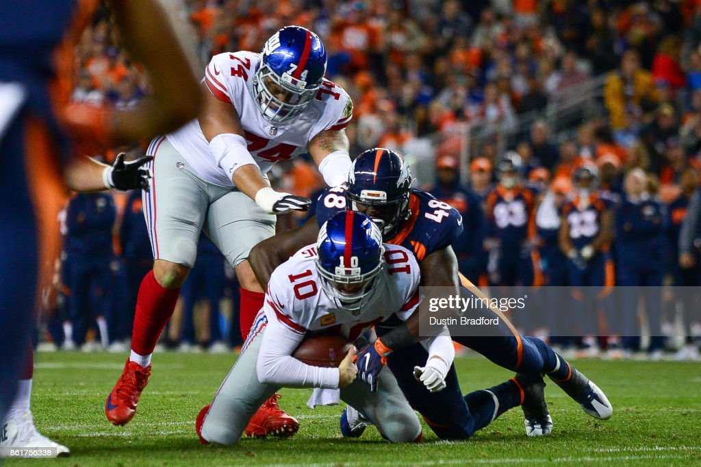 Quarterback Eli Manning #10 of the New York Giants is sacked by outside linebacker Shaquil Barrett #48 of the Denver Broncos in the red zone on third down in the first quarter of a game is at Sports Authority Field at Mile High on October 15, 2017 in Denver, Colorado.