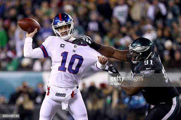 Quarterback Eli Manning of the New York Giants looks to throw a pass against defensive tackle Fletcher Cox of the Philadelphia Eagles during the...