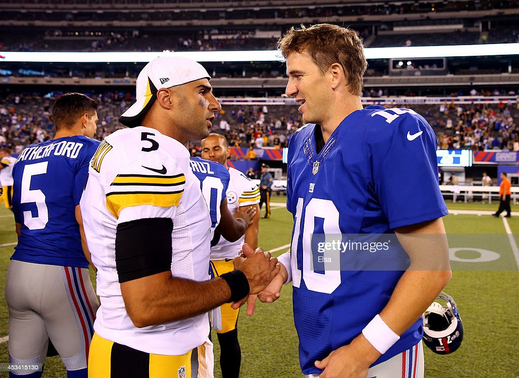 Quarterback Eli Manning #10 of the New York Giants meets with quarterback Bruce Gradkowski #5 of the Pittsburgh Steelers following a preseason game at MetLife Stadium on August 9, 2014 in East Rutherford, New Jersey.