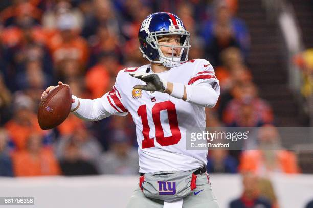 Quarterback Eli Manning of the New York Giants passes against the Denver Broncos in the first quarter of a game at Sports Authority Field at Mile...