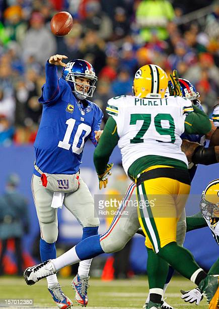 Quarterback Eli Manning of the New York Giants throws a pass before Ryan Pickett of the Green Bay Packers can get to him during a game at MetLife...