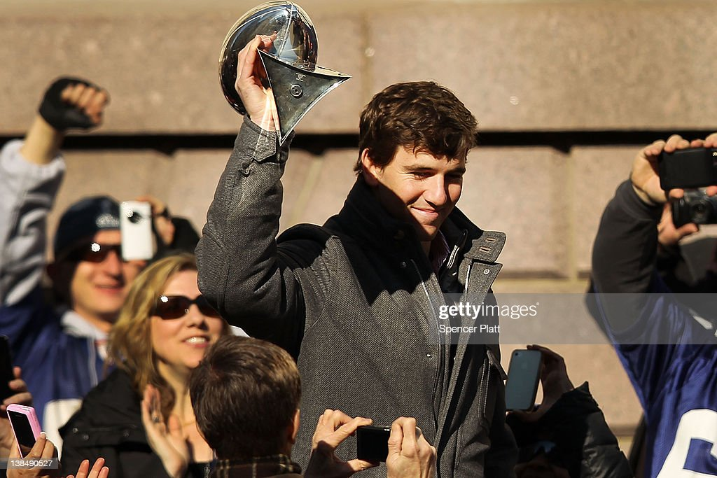 Quarterback Eli Manning of the New York Giants walks onto stage as the team is honored at City Hall Plaza following a ticker-tape parade in Manhattan for the second time in four years after winning the Super Bowl against the New England Patriots on February 7, 2012 in New York City. The Giants beat the Patriots 21-17 at Lucas Oil Stadium in Indianapolis on February 5. The New York parade started at Battery Place and continued through the financial district, an area known as the 'Canyon of Heroes,' to be followed by a rally at their home MetLife Stadium in East Rutherford, New Jersey.