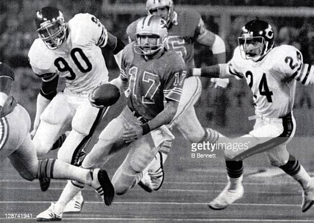 Quarterback Eric Hipple of the Detroit Lions runs past Al Harris and Jeff Fisher of the Chicago Bears on October 19 1981 at the Pontiac Silverdome in...