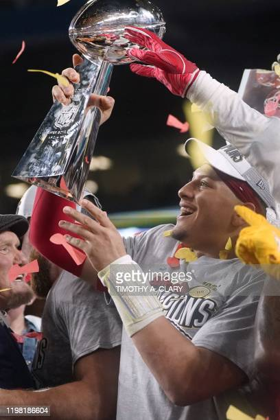Quarterback for the Kansas City Chiefs Patrick Mahomes holds up the Vince Lombardi Trophy as he celebrates with teammates on the podium after winning...