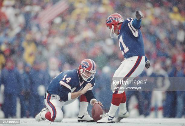 Quarterback Frank Reich holds the ball as Scott Norwood and Kicker for the Buffalo Bills attempts a field goal in the snow during their American...