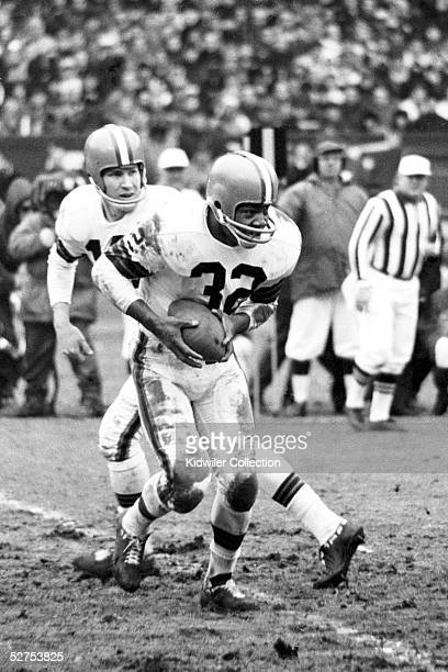 Quarterback Frank Ryan of the Cleveland Browns hands the ball to runningback Jim Brown during a game in 1964 at Municipal Stadium in Cleveland Ohio