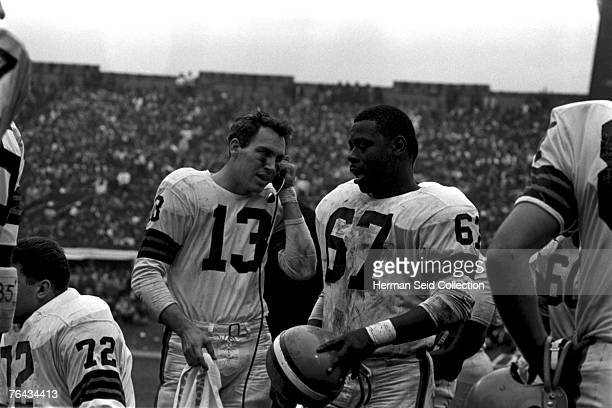 Quarterback Frank Ryan of the Cleveland Browns uses a headset from the sidelines to talk to the coaches watching the action from the top of the...